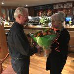 Jan Meijer ontvangt van Henny Kars namens de biljartvereniging een bos bloemen bij zijn 40-jarig jubileum als lid van Metropole